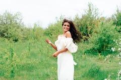 Härlig ung flicka i den vita klänningen i våren som blomstrar äpplefruktträdgårdar Royaltyfri Fotografi