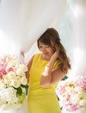 Härlig ung flicka i en gul klänning på terrassen bakgrunden av nya blommor Fotografering för Bildbyråer