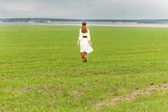 Härlig ung flicka i en vit klänning med långt hår på fältet på en molnig dag Royaltyfri Fotografi