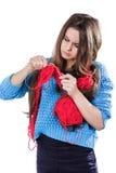 Härlig ung flicka i ett blått tröjaanseende med ett rött garnnystan och handarbete en halsduk och en Spitz Vit bakgrund isolate Royaltyfria Foton