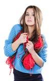 Härlig ung flicka i ett blått tröjaanseende med ett rött garnnystan och handarbete en halsduk och en Spitz Vit bakgrund isolate Royaltyfri Fotografi