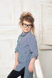 Härlig ung flicka i exponeringsglas som sitter på trappan av det ljusa rummet Arkivfoto