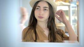 Härlig ung flicka i hatten som ser sig i spegel skönhet för begreppslivsstilmode arkivfilmer