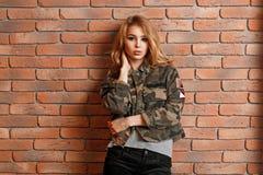 Härlig ung flicka i militärt omslag nära väggen för röd tegelsten royaltyfria foton