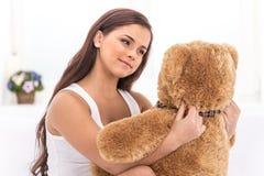 Härlig ung flicka i säng som ser nallebjörnen Arkivbild