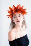 Härlig ung flicka i svarta linser med liljor Royaltyfria Foton