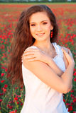 Härlig ung flicka i vallmofält Arkivfoto