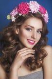 Härlig ung flicka med en blom- prydnad i hennes hår på en blå bakgrund blommar kvinnakranen Härlig le flicka Modephot arkivbild
