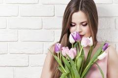 Härlig ung flicka med en bukett av tulpan Stående Blommor i händerna av flickan Arkivfoto