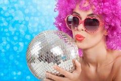 Härlig ung flicka med en rosa peruk som rymmer en diskoboll Royaltyfri Bild