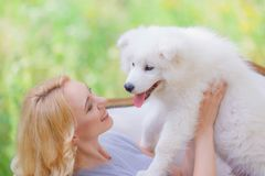 Härlig ung flicka med en vit valp i hennes armar på en retro soffa i en sommarträdgård royaltyfri bild