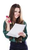 Härlig ung flicka med ett stort stycke av papper och en blyertspenna på en vit bakgrund Fotografering för Bildbyråer