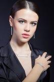 Härlig ung flicka med härliga stilfulla dyra smycken, halsband, örhängen, armband, cirkel som filmar i studion fotografering för bildbyråer