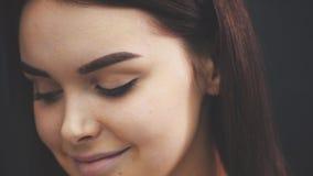 Härlig ung flicka med härligt långt anseende för mörkt hår på en svart bakgrund Detta är ett leende på den tiden stock video
