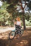 Härlig ung flicka med hennes cykelkryssare och blommor på höstfält Den bästa tiden att gå med en cykel Royaltyfri Bild