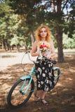 Härlig ung flicka med hennes cykelkryssare och blommor på höstfält Den bästa tiden att gå med en cykel Arkivfoto