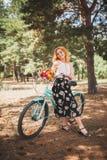 Härlig ung flicka med hennes cykelkryssare och blommor på höstfält Den bästa tiden att gå med en cykel Royaltyfri Foto