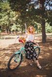 Härlig ung flicka med hennes cykelkryssare och blommor på höstfält Den bästa tiden att gå med en cykel Royaltyfria Foton