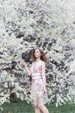 Härlig ung flicka med krullning i en luft färgad klänning med en krans på hennes huvud som går i parkera nära en körsbärsröd blom arkivfoton