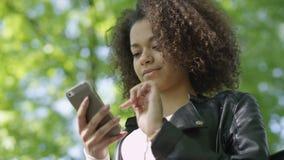 Härlig ung flicka med mörkt lockigt hår genom att använda hennes mobiltelefon som är utomhus- arkivfilmer
