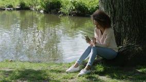 Härlig ung flicka med mörkt lockigt hår genom att använda hennes mobiltelefon som är utomhus- stock video