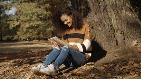 Härlig ung flicka med mörkt lockigt hår genom att använda minnestavladatoren som är utomhus- lager videofilmer
