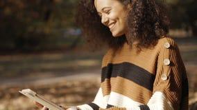 Härlig ung flicka med mörkt lockigt hår genom att använda minnestavladatoren som är utomhus- stock video