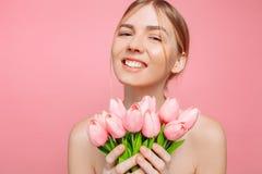 Härlig ung flicka med ren hud som rymmer en bukett av rosa tulpan, på en rosa bakgrund royaltyfria foton