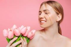Härlig ung flicka med ren hud som rymmer en bukett av rosa tulpan, på en rosa bakgrund arkivbild