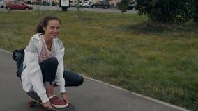 Härlig ung flicka med ryggsäckridninglongboard i skateboarding student för solig väderskateboardskateboradåkare lager videofilmer