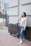Härlig ung flicka med stoppat långt brunt hår, medan rida sparkcykeln, för att kalla en vän på telefonen på bakgrunden av Royaltyfria Bilder