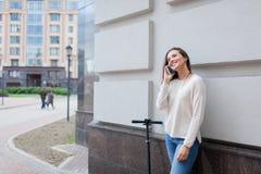 Härlig ung flicka med stoppat långt brunt hår, medan rida sparkcykeln, för att kalla en vän på telefonen på bakgrunden av Royaltyfri Bild