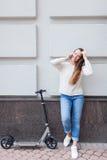 Härlig ung flicka med stoppat långt brunt hår, medan rida sparkcykeln, för att kalla en vän på telefonen på bakgrunden av Fotografering för Bildbyråer