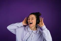 Härlig ung flicka med vita tänder som lyssnar till musik och sjunger högt i hörlurar i en tröja på en lila fotografering för bildbyråer