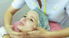 Härlig ung flicka på en ansikts- massage lager videofilmer