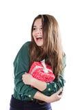 Härlig ung flicka på en vit bakgrund som rymmer en ask med en gåva leenden Arkivbilder