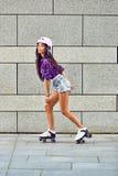 Härlig ung flicka som åker skridskor på rullskridskor royaltyfria bilder