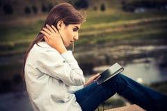Härlig ung flicka som använder den digitala minnestavlan Royaltyfri Fotografi