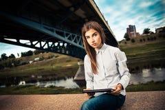 Härlig ung flicka som använder den digitala minnestavlan Fotografering för Bildbyråer