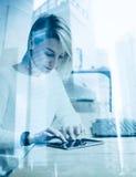 Härlig ung flicka som använder den moderna minnestavlan på trätabellen Begrepp av coworking folk som arbetar med grejer double royaltyfria foton