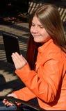 Härlig ung flicka som använder en minnestavla Royaltyfri Bild