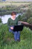 Härlig ung flicka som använder hennes sammanträde för grafisk minnestavla i gräset Arkivbilder