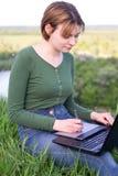 Härlig ung flicka som använder hennes sammanträde för grafisk minnestavla i gräset Royaltyfri Foto