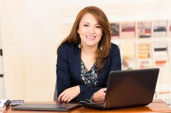 Härlig ung flicka som arbetar bak ett skrivbord med Royaltyfri Fotografi