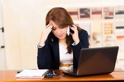 Härlig ung flicka som arbetar bak ett skrivbord med Arkivbild