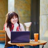 Härlig ung flicka som arbetar eller studerar i kafé Arkivbild