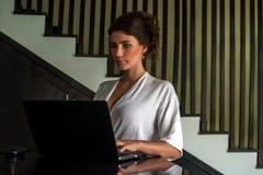 Härlig ung flicka som arbetar på det moderna stället med en bärbar dator Kvinnlig freelancer som förbinder till internet via dato royaltyfri bild