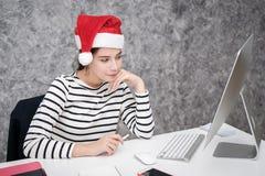 Härlig ung flicka som bär en santa julhatt Arkivfoto