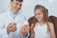 Härlig ung flicka som besöker tandläkaren royaltyfri foto