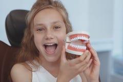 Härlig ung flicka som besöker tandläkaren royaltyfria foton